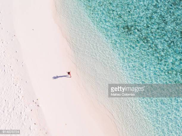 overhead view of woman walking on a beach, maldives - idyllic stock pictures, royalty-free photos & images