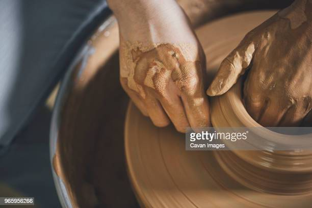 overhead view of woman working on pottery wheel at workshop - clay stock pictures, royalty-free photos & images