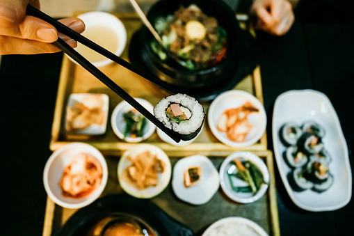 Overhead view of woman's hand eating kim bap with chopsticks against fresh Korean meal in restaurant - gettyimageskorea
