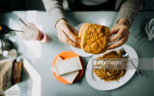 Overhead view of woman's hand holding Hong Kong style local foods, sandwich, buttered pineapple bun, fried noodles and iced red bean drink in traditional restaurant