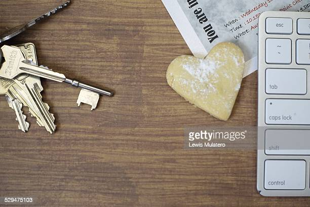 Overhead view of wooden desk with computer keyboard Paper party invite set of keys and a heart shape cookie