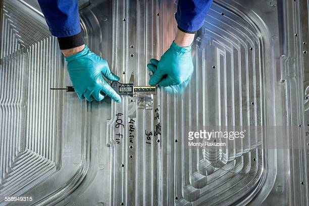 Overhead view of worker finishing metal mould in plastics factory, close up
