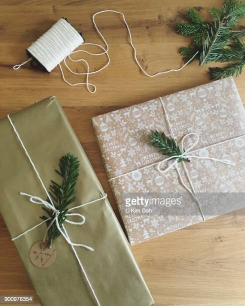 Overhead view of wrapped Christmas presents with fir leaf decoration on wooden table
