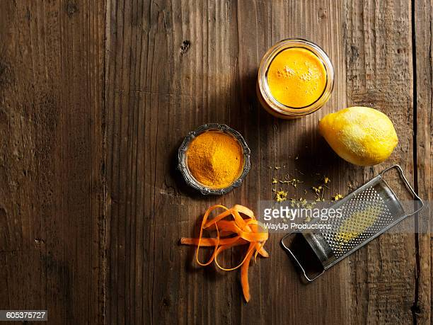 Overhead view of yellow raw juice with grated lemon and carrot on wood grain pattern background