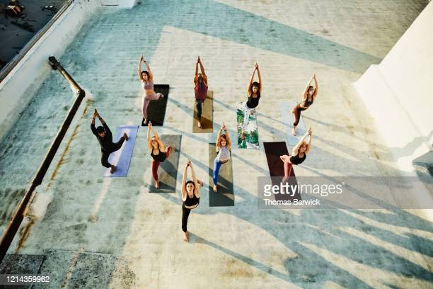 overhead view of yoga class in warrior pose while practicing on rooftop - yoga stock pictures, royalty-free photos & images