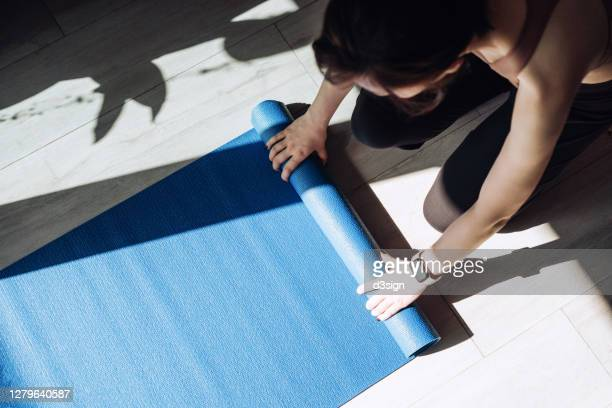 overhead view of young asian sports woman practicing yoga / exercising at home. unrolling yoga mat, getting prepared to work out in the fresh bright morning - de rola imagens e fotografias de stock