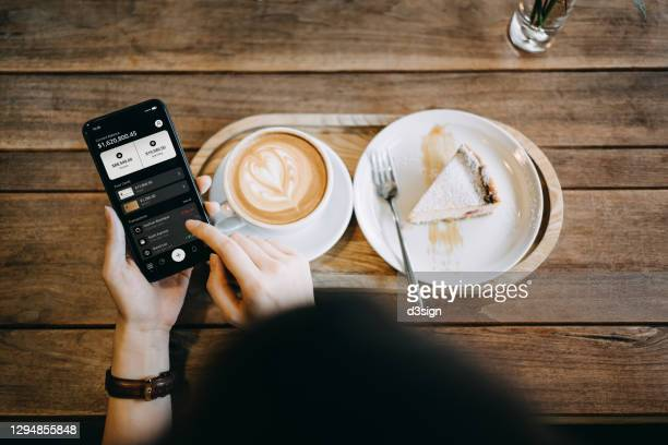 overhead view of young asian woman managing online banking with mobile app on smartphone. transferring money, paying bills, checking balances while enjoying a cup of coffee and cake at home. technology makes life so much easier - hong kong stock pictures, royalty-free photos & images