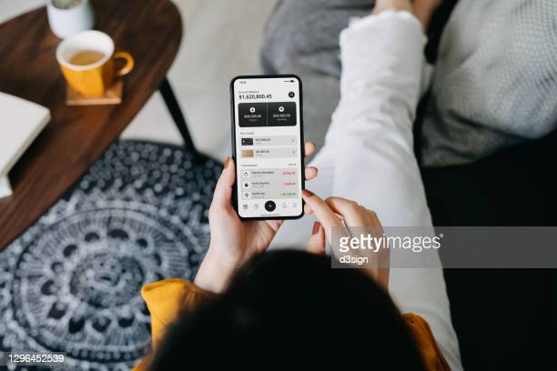 overhead view of young asian woman relaxing on the sofa in the living room, managing online banking with smartphone at cozy home. transferring money, paying bills, checking balances. technology makes life so much easier - bank account stock pictures, royalty-free photos & images