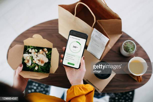 overhead view of young asian woman using health and fitness plan mobile app on smartphone to tailor make her daily diet meal plan, checking the nutrition facts and calories intake of the home delivery takeaway grilled chicken salad lunch box at home - customer engagement stock pictures, royalty-free photos & images