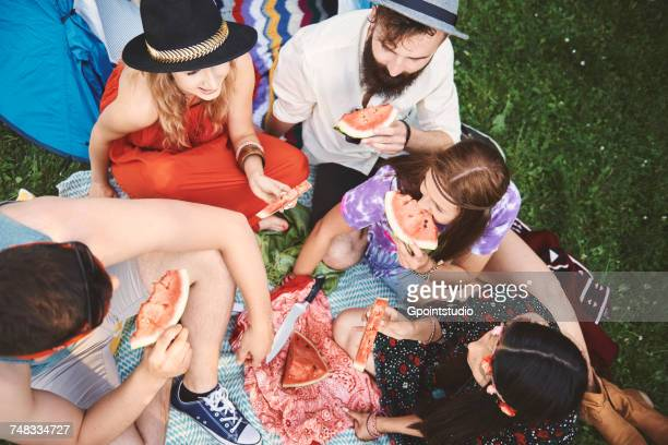 Overhead view of young boho adult friends eating melon slices at festival