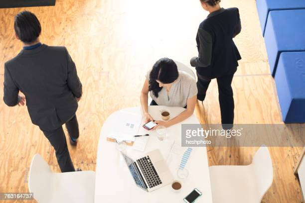 overhead view of young businesswoman looking at smartphone at office table - heshphoto stock pictures, royalty-free photos & images