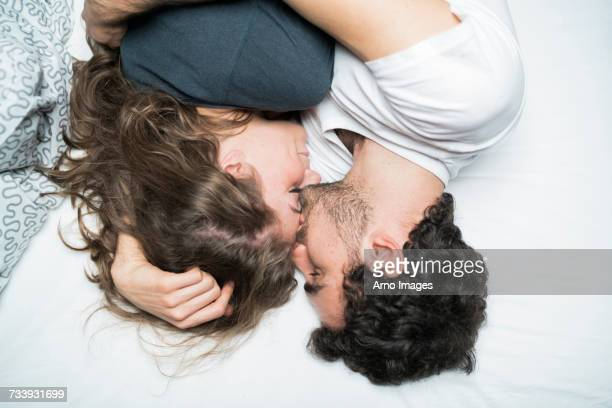 overhead view of young couple lying in bed embracing - florence douillet photos et images de collection