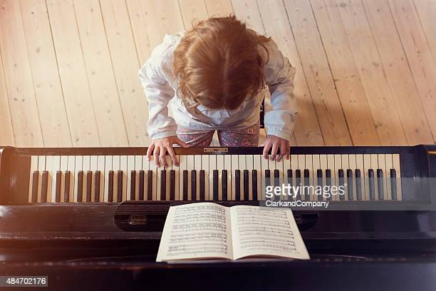 overhead view of young girl playing piano in sunlight room - keyboard player stock photos and pictures