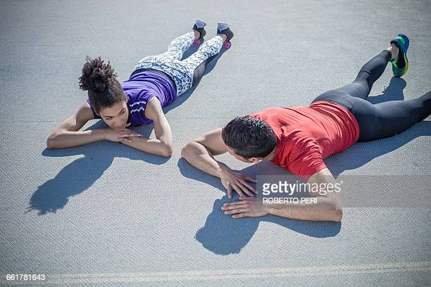 Overhead view of young man and woman training, taking a break on asphalt