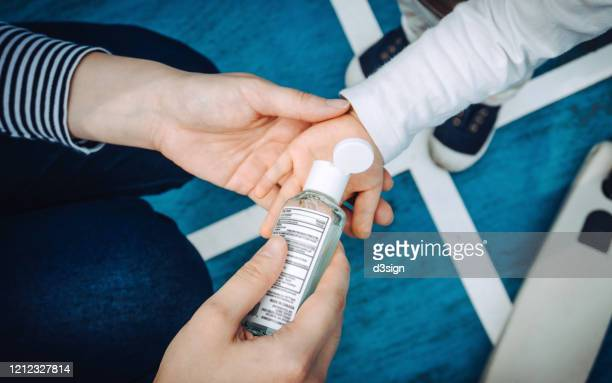 overhead view of young mother squeezing hand sanitizer onto little daughter's hand in the playground to prevent the spread of viruses - hand sanitizer stockfoto's en -beelden