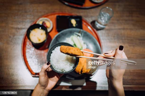 overhead view of young woman enjoying freshly served traditional japanese meal set. miso soup, appetizers and tonkatsu (deep fried pork cutlets) in a japanese restaurant - tonkatsu imagens e fotografias de stock