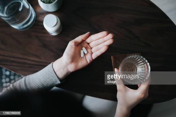 overhead view of young woman holding a glass of water, taking medicines at home. medicine, healthcare and people concept - anti depressant stock pictures, royalty-free photos & images