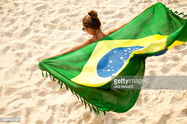 Overhead view of young woman holding Brazilian flag whilst dancing, Ipanema beach, Rio De Janeiro, Brazil