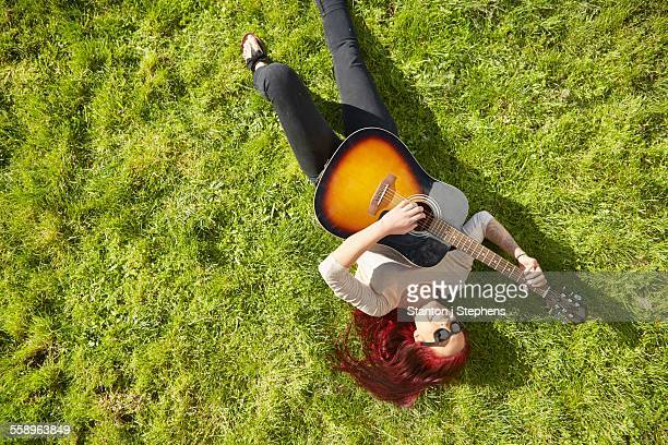 Overhead view of young woman lying on grass playing acoustic guitar