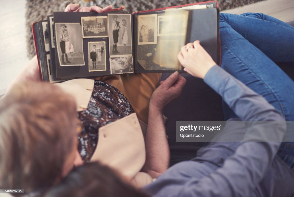 Overhead view of young woman on sofa with grandmother looking at photo album : Stock Photo