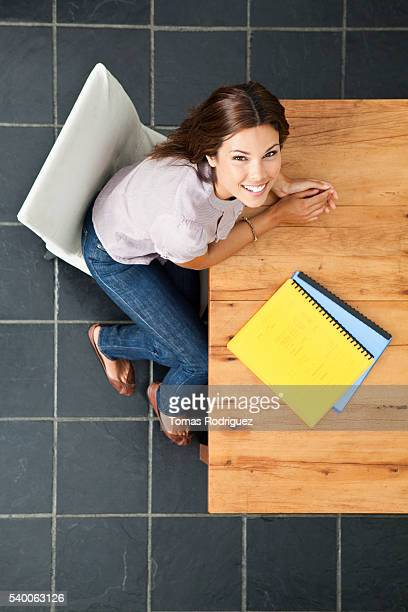 Overhead view of young woman sitting at kitchen table
