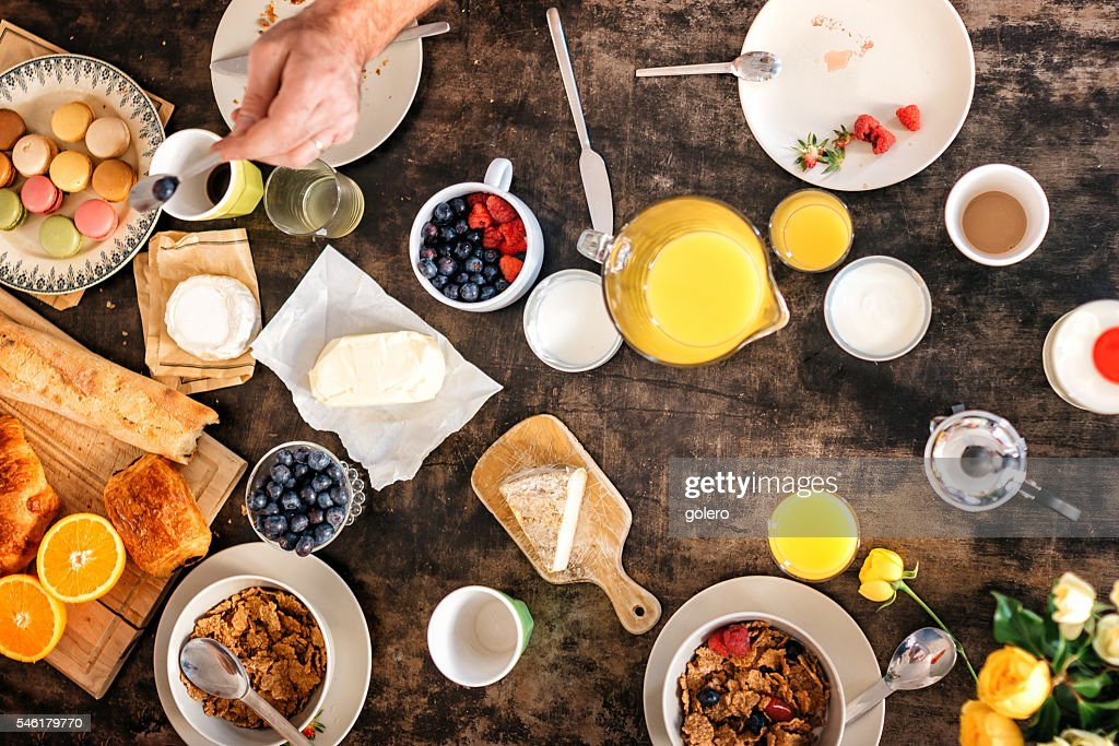 overhead view on breakfast table with macarons, baguette and fruits : Stock-Foto