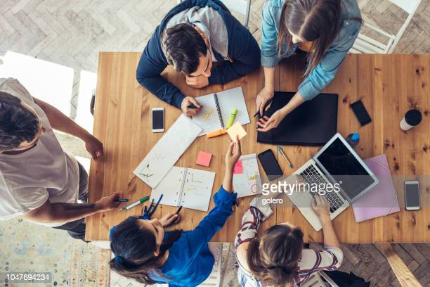 overhead view on business people around desk - cooperation stock pictures, royalty-free photos & images