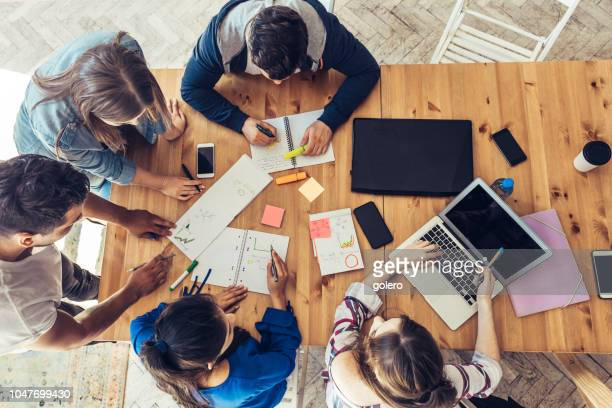 overhead view on business people around desk - strategia foto e immagini stock
