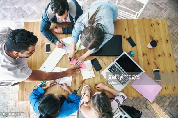 vista general de los empresarios que trabajan juntos en el escritorio - marketing fotografías e imágenes de stock