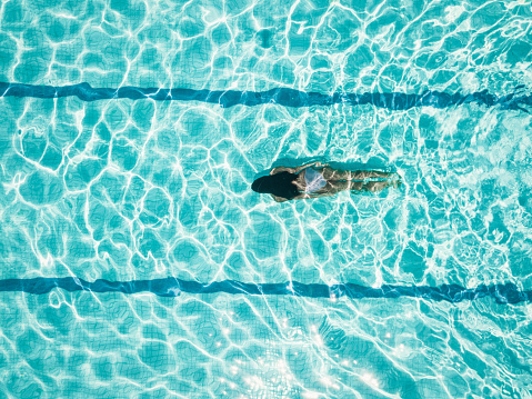 overhead view on girl idiving in swimming pool 1091848622