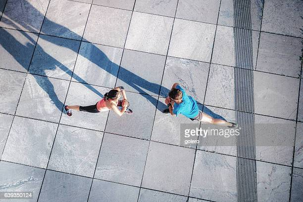 overhead view on woman and man stretching on city square