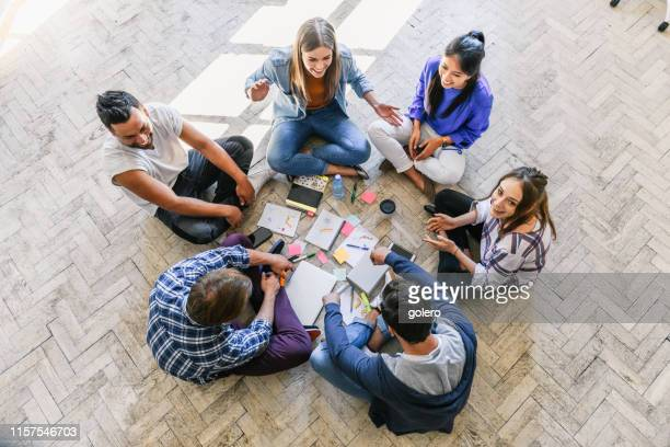 overhead view on young people sitting in a circle on floor - medium group of people stock pictures, royalty-free photos & images