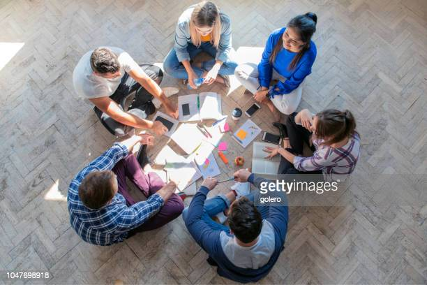 overhead view on young people sitting on floor - small group of people stock pictures, royalty-free photos & images