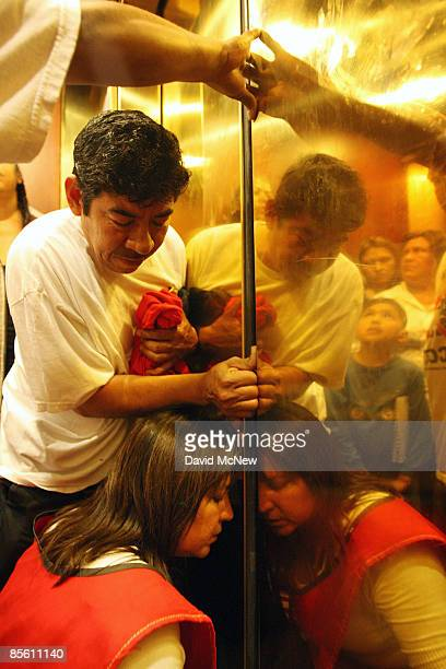 Overheated homeowners and ACORN activists try to force the doors open a crack to let in fresh air after becoming stuck in an elevator as they visit...