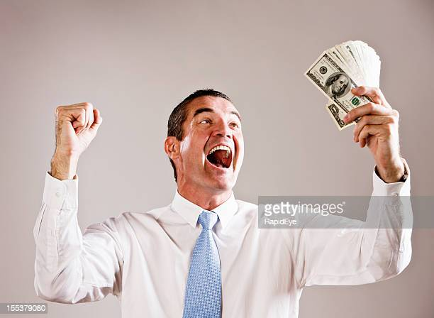 overjoyed businessman with fistful of dollars - winnings stock photos and pictures