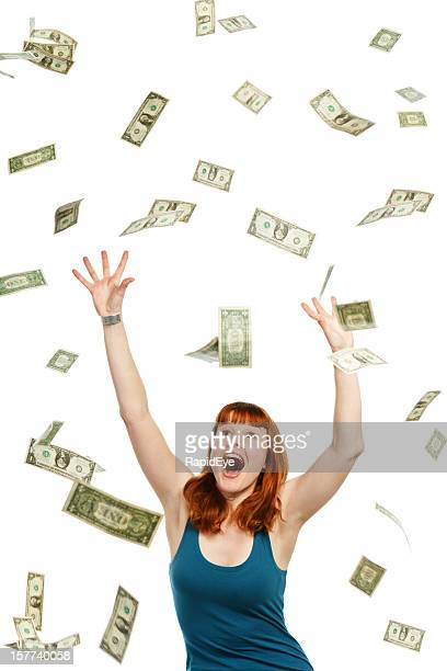 Overjoyed young redhead catching shower of falling banknotes