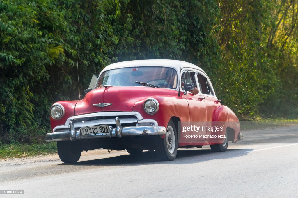 Overloaded red Chevrolet vintage car on a rural road. When ...