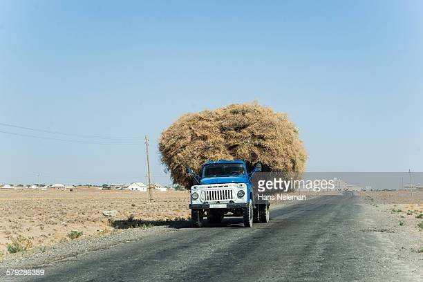 Overloaded truck hauling hay on rural road