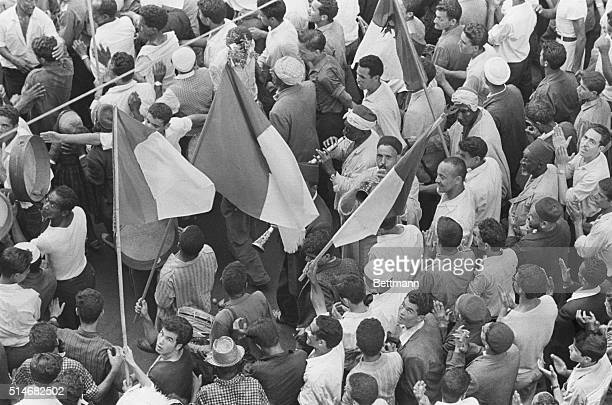 Overlooking Muslims waving the Algerian national flag and playing traditional music instruments while celebrating the July 1st Independence Day.  ...