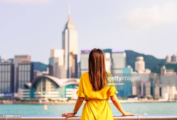 overlooking victoria harbour in hong kong - yellow dress stock pictures, royalty-free photos & images