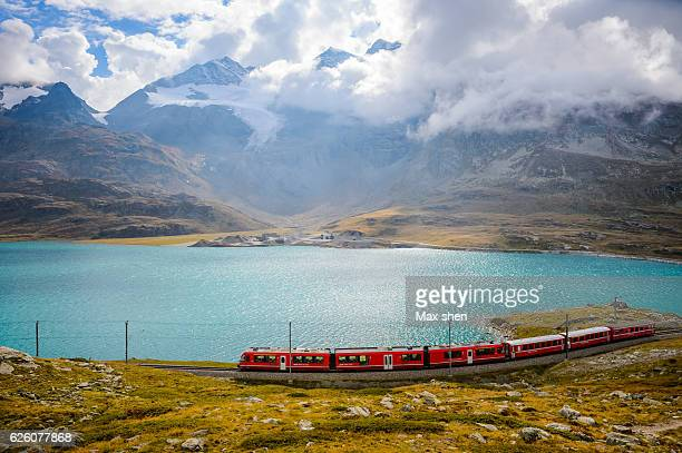 overlooking view of train running on the bernina railway in switzerland. - passenger train stock pictures, royalty-free photos & images