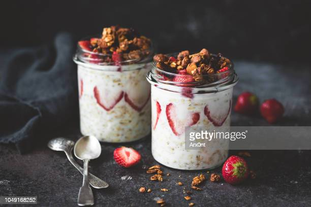 overnight oats with strawberries and granola in jar - dessert stock-fotos und bilder
