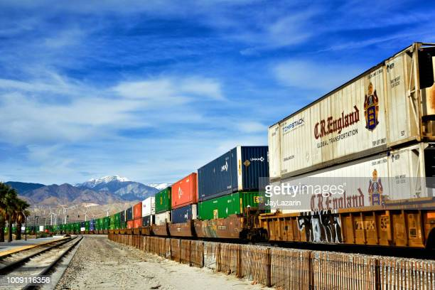 overseas cargo containers and u.s. truck trailers on union pacific freight train, palm springs, california, usa - rail freight stock pictures, royalty-free photos & images