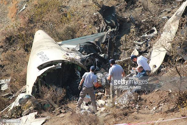 Overseas investigators examine the wreckage of a Pakistan International Airlines passenger plane which crashed near the village of Saddha Batolni in...