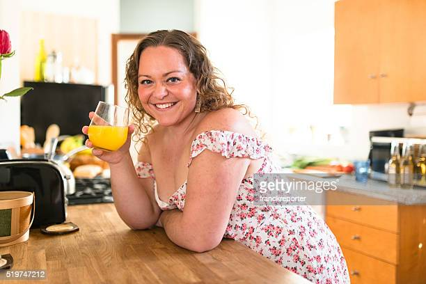 oversize woman drinking orange juice at home