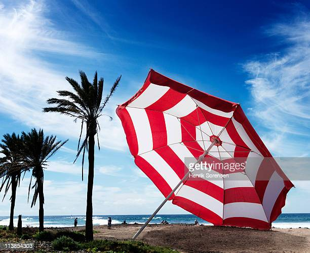 Oversized beach parasol resting on the sand