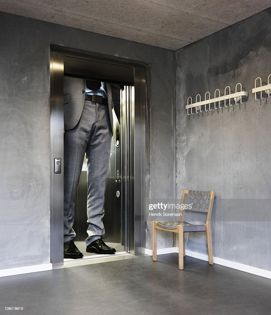 Oversized businessman in an elevator : Stock Photo
