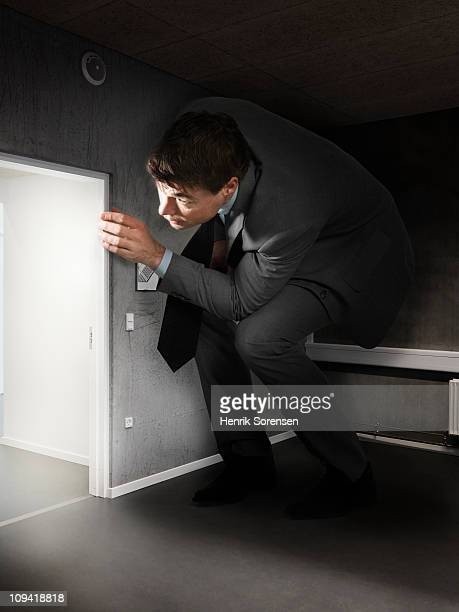Oversized businessman peeking around a corner