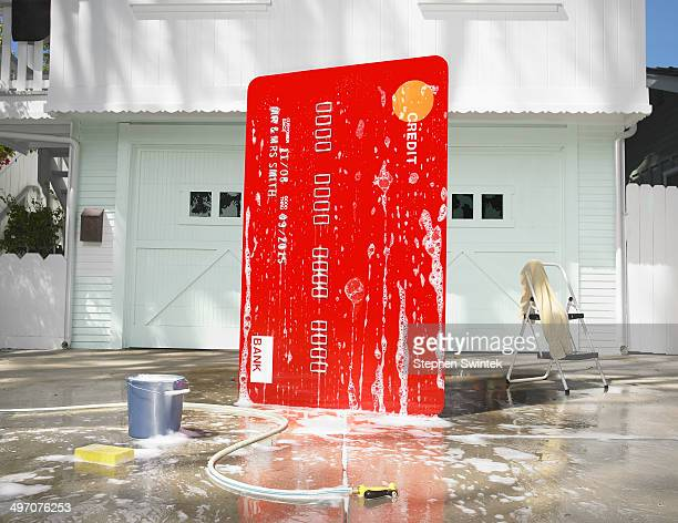 Oversized credit card being washed in a driveway