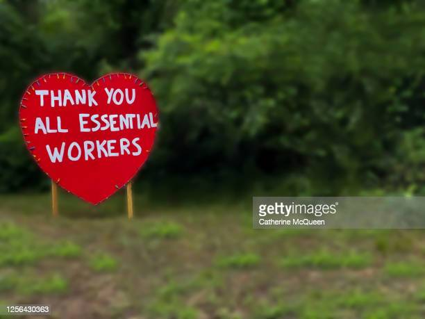 oversized heart-shaped road thank you sign for essential workers during covid-19 pandemic - thank you stock pictures, royalty-free photos & images